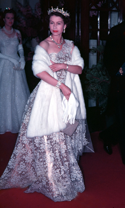 Pairing a stole with an elegant evening gown was the Queen's go-to theatre ensemble in the 1950s. 