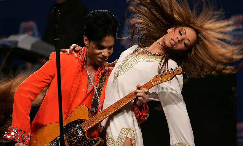 Playing his guitar with a lady on his arm during the press conference for his Super Bowl halftime show performance in Miami in 2007. 