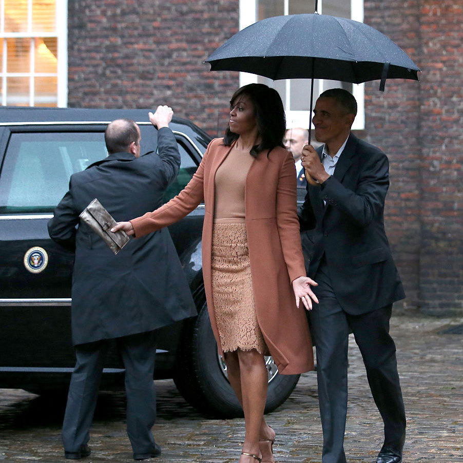 "A little rain didn't bother the first lady as she exited her car at Kensington Palace. In fact, earlier in the day, President Obama said during a press conference with Prime Minister David Cameron that he ""warmed up"" for important meetings Friday morning by playing a couple classic Prince songs including ""Purple Rain"".