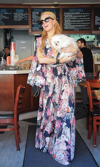 Paris Hilton brought her furry friend along on a coffee run in Los Angeles. The animal lover wore a floral maxi and bohemian headband as she cradled one of her many beloved pups.