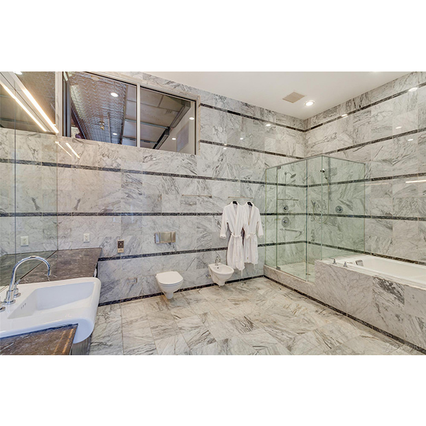 The bathroom features floor-to-ceiling tiling, a walk-in shower and jacuzzi bathtub. 
