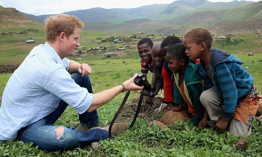 Harry was snapped showing children photographs of his trip as he visited a herd boy night school. The school was constructed by Sentebale, the Prince's charity that provides healthcare and education to children in Lesotho.