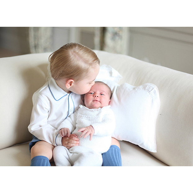 For Princess Charlotte's first official portraits, taken in Norfolk on June 6  2015, Kate turned photographer for the day. Proud big brother Prince George kisses his sister's head gently.