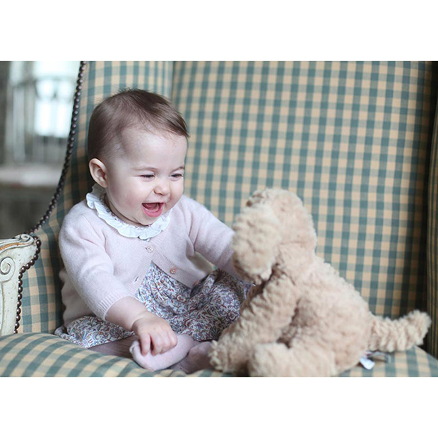 Princess Charlotte shows off her infectious smile, looking very grown up at six months old, as she plays with her teddy bear.
