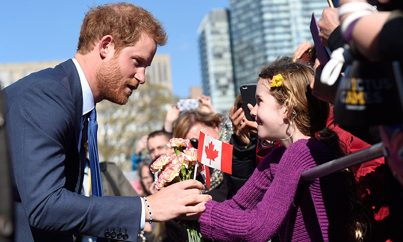 After waiting patiently for Prince Harry to leave his meeting at Queen's Park, this young fan got the chance to present some beautiful roses to the prince.<br>Photo: © Nathan Denette/CP