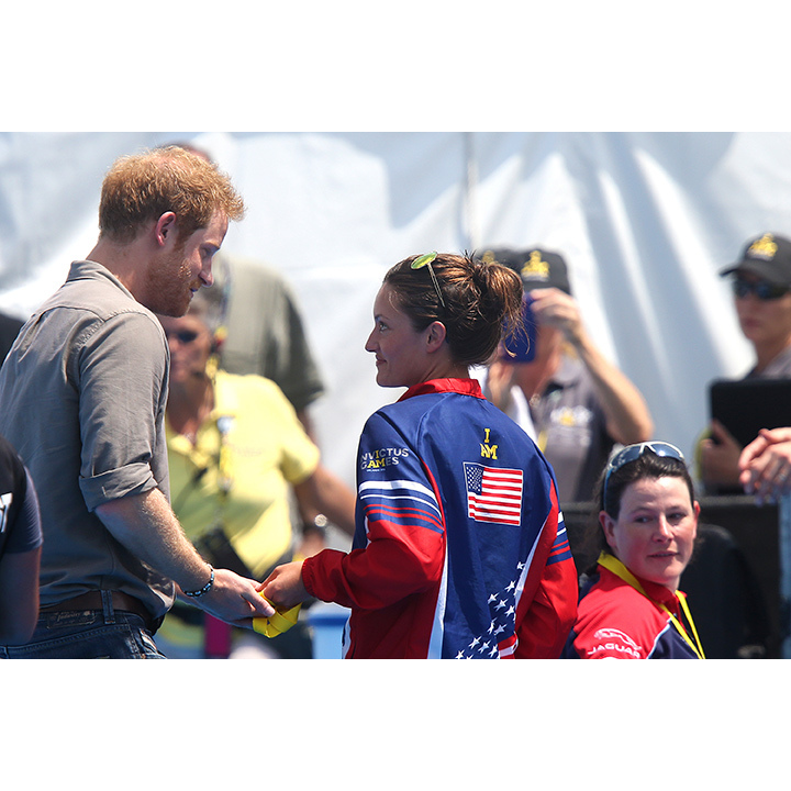 Here, Harry shares a poignant moment with Team USA's Sergeant Elizabeth Marks after her gold medal-winning performance in freestyle swimming. Elizabeth returned the medal and asked Harry to donate it to a British hospital that saved her life. 