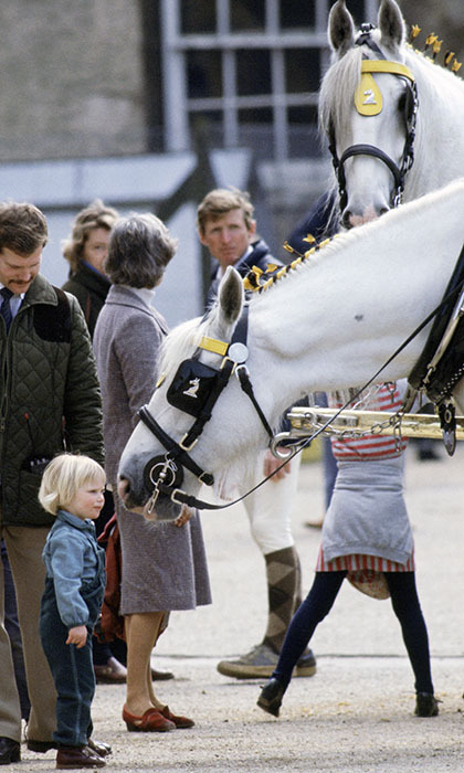 A young Zara Tindall, age two, gets up close and personal with a steed at the Badminton Horse Trials in 1984. <p>Photo: © Getty Images</p>