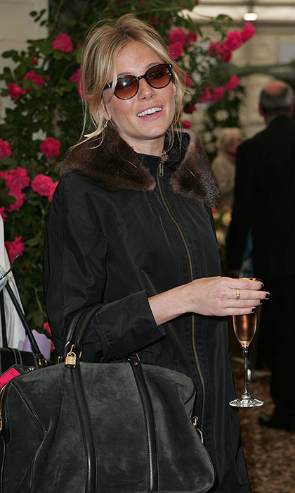 Sunglasses-clad Sienna Miller enjoyed a glass of champagne during the opening of the Chelsea Flower Show in 2009.