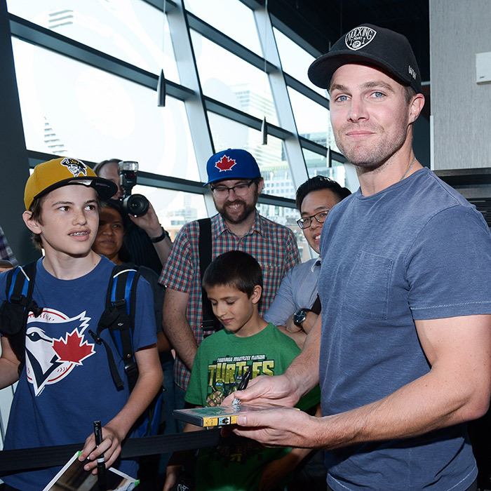 A known Toronto Blue Jays fan, the <em>Arrow</em> star signs autographs for fans on the red carpet.