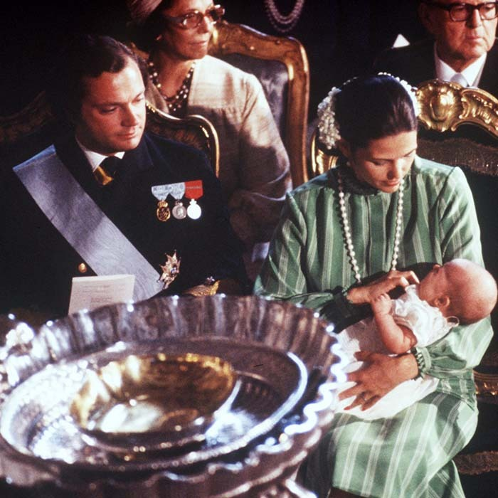 King Carl Gustaf and his wife Queen Silvia cradle their newborn baby girl and heir to the throne Crown Princess Victoria during her baptism in 1977. 