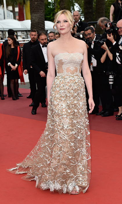 Kirsten Dunst stuns on the red carpet at Cannes in a sheer and floral-embellished Valentino gown with a lacy corset and bold red lip for a pop of colour.