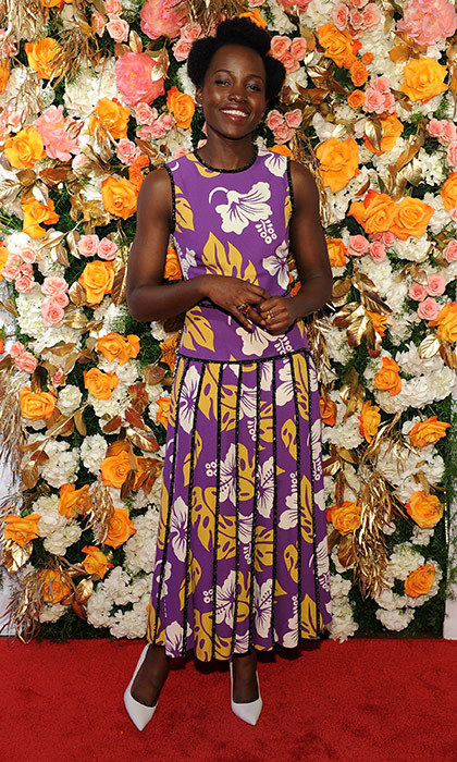 Lupita Nyong'o looks garden party-ready in a floral-printed Prada gown and white pointy pumps at the Obie Awards in New York.