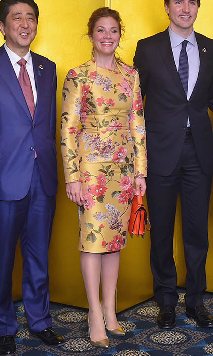 A cocktail event during the G7 Japan 2016 Ise-Shima summit brought out another stunning floral dress, this time in a golden hue and designed by Wayne Clark, which she paired with an orange Mackage bag, Jon de Jong earrings and metallic Zvelle shoes. 