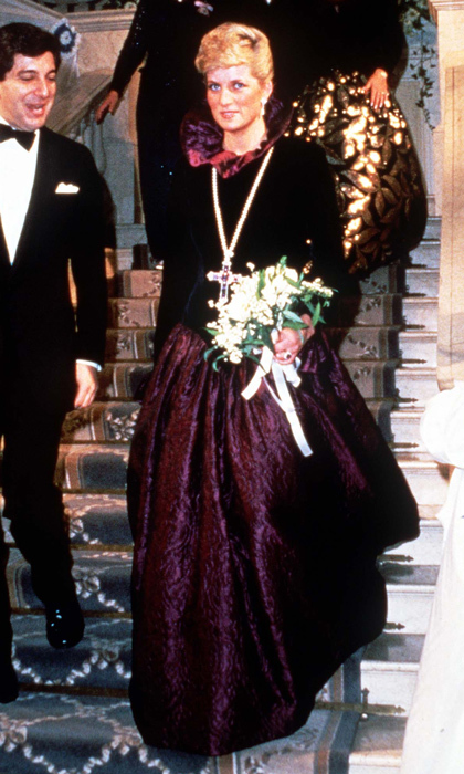 "The highly charitable royal was on hand at a function on behalf of Birthright at Garrard the Jewellers in 1987, where this black and deep-purple <strong><a href=""/tags/0/catherine-walker"">Catherine Walker</a></strong> gown with ruffled collar and cross necklace gave Diana's ensemble a Victorian feel. 