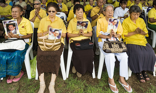 The king's loyal supporters clutched photographs of the royal and prayed for him.