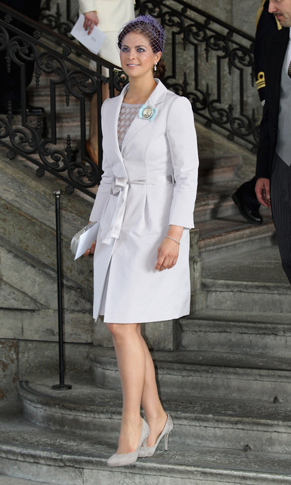 Princess Madeleine sported a classic white coat dress, belted delicately at the waist, with grey pumps, a metallic clutch and a purple birdcage veil at the christening of her niece, Princess Estelle. 