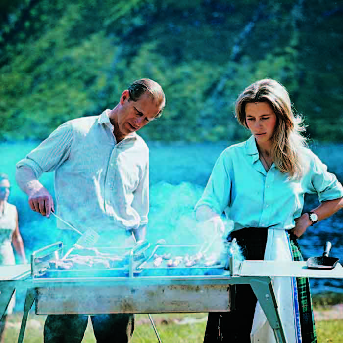 The Duke loves a good cookout. Here, Philip masters the barbecue with a little help from his daughter Princess Anne during the family's summer holiday at Balmoral in 1971. 