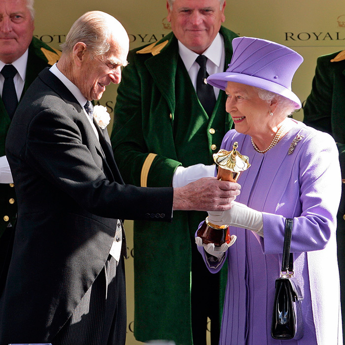 Prince Philip presented his wife with a winning owner's trophy after her horse, Estimate, won the Queen's Vase in 2012.