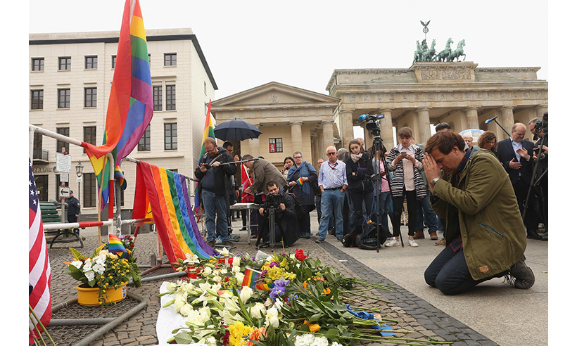 Flowers and flags were placed at a vigil in Berlin. 