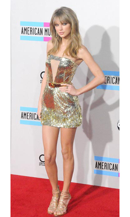 Showing off her incredibly long legs in a gold minidress.