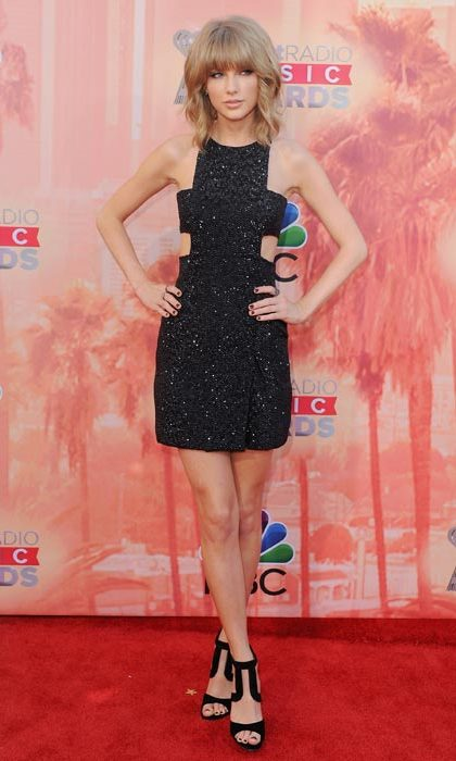Showing off her slim frame in a black cutout sparkly minidress.