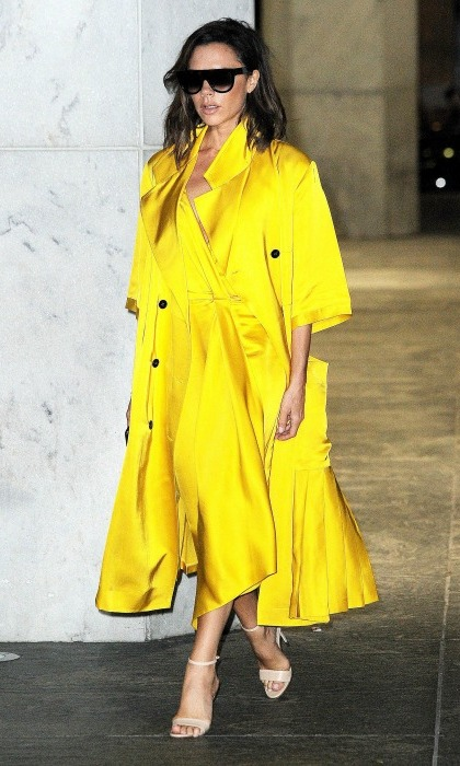 Victoria Beckham stepped out in Manhattan glowing in a bold yellow coat and matching dress, which she expertly paired with nude heels.