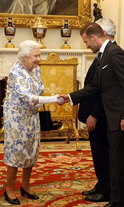 The Queen greets David Beckham in a floral dress and white gloves at Buckingham Palace on Thursday.