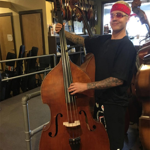 Justin Bieber holding a double bass