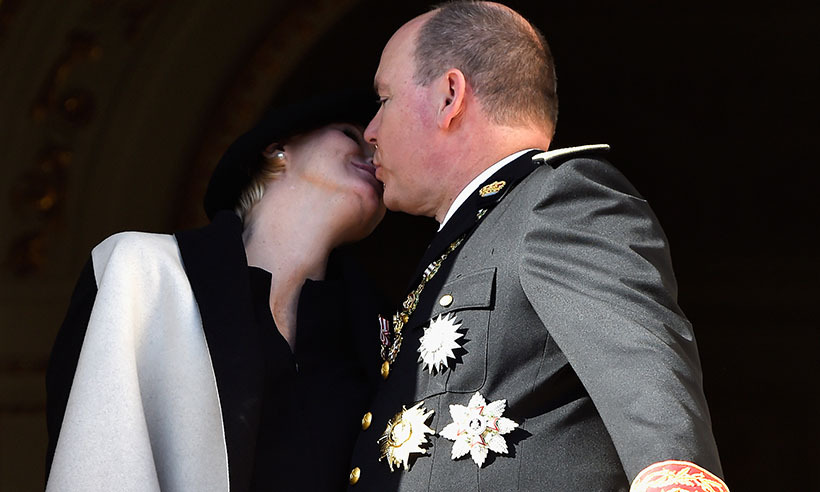 The happy couple steal a kiss on the palace's balcony during the National Day Parade in 2014, part of the annual Monaco National Day celebrations. 