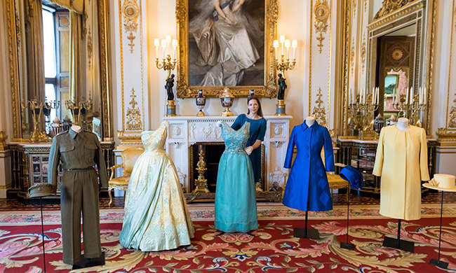 Caroline de Guitaut, Senior Curator at The Royal Collection, poses for a picture in the White Drawing Room with an Auxiliary Territorial Service overalls and cap worn by Princess Elizabeth whilst serving in the wartime ATS, a pale blue and gold evening dress by Sir Norman Hartnell, a turquoise silk shift dress with silver floral embroidery by Hardy Amies, an outfit and hat designed by Sir Norman Hartnell, an outfit and hat designed by Angela Kelly during the exhibition preview for 'Fashioning a Reign: 90 Years of Style from The Queen's Wardrobe' at Buckingham Palace.