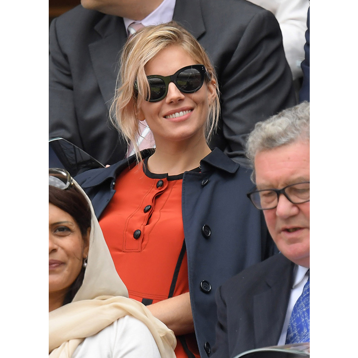 Sienna Miller stood out from the crowd in a pleated Burberry dress and sunnies on day nine of competition. 