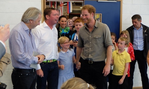 Harry held hands with a little girl, while visiting the Wigan Youth Zone.