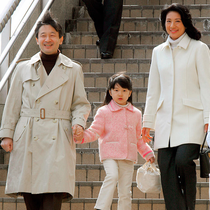 Pretty in pink! The little Princess held on tightly to her father's hand as the trio arrived at the Nagano station in central Japan on their way to their annual ski trip.
