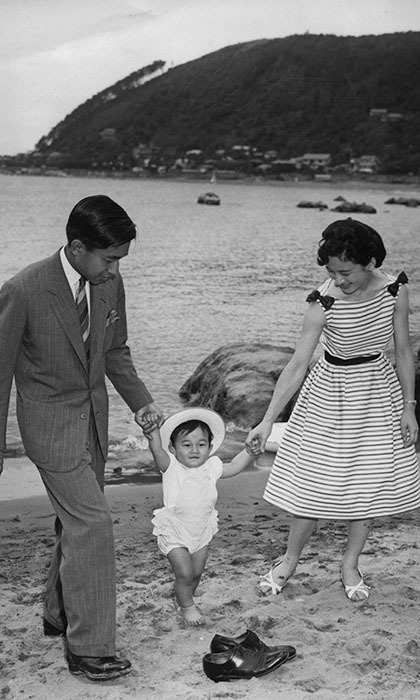 A young Prince Naruhito walks on the beach near the Hayama Imperial Villa with his parents, Crown Prince Akihito and Princess Michiko in 1961. 
