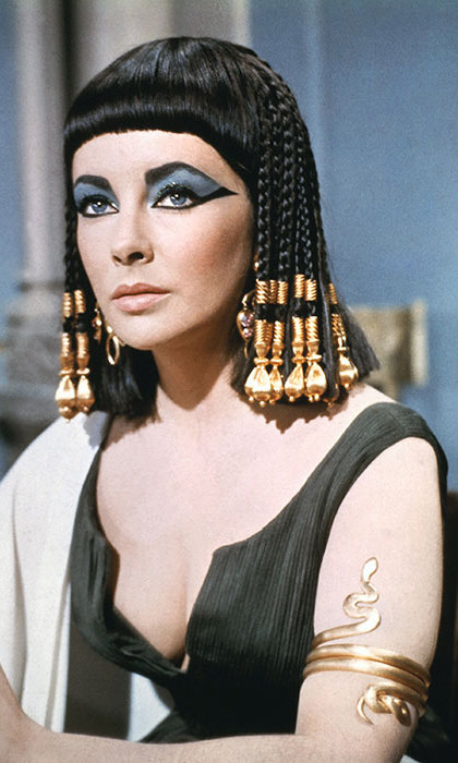 Elizabeth Taylor's hairstyle in <em><strong>Cleopatra</strong></em> remains one of film's iconic looks, with its golden accessories, braids and blunt full fringe. 