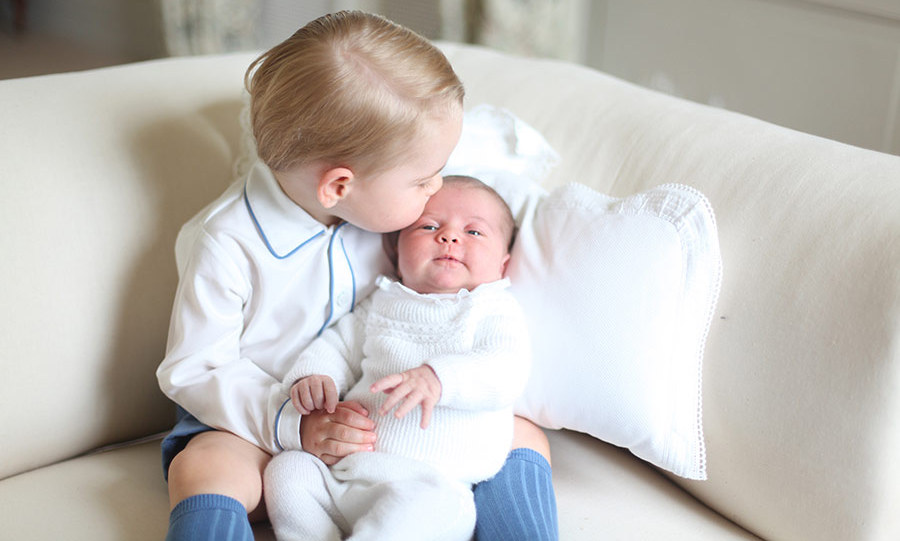 George looked like a proud big brother as he placed a gentle kiss on his baby sister Princess Charlotte, in their first offical portraits together.