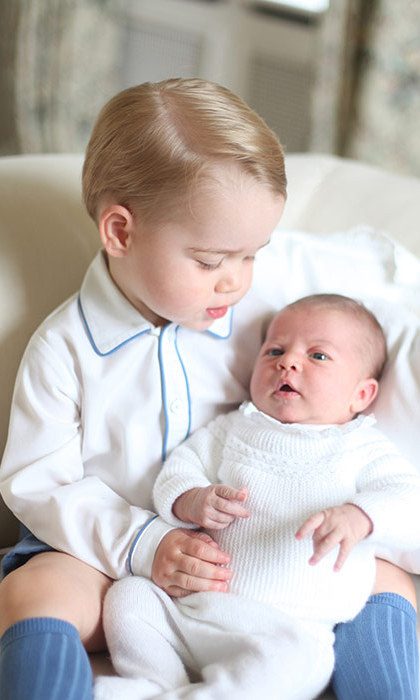 The future King kept a watchful eye on his baby sister in the sweet portraits.
