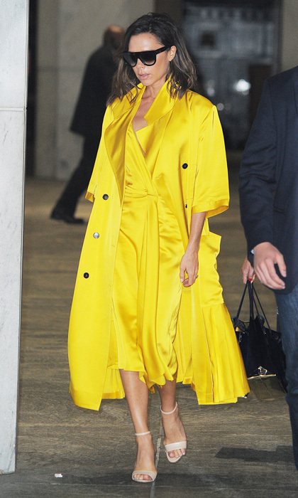 Victoria Beckham stepped out of her traditional muted palette in favour of a bright, silk coat and dress set from her eponymous fashion label. 