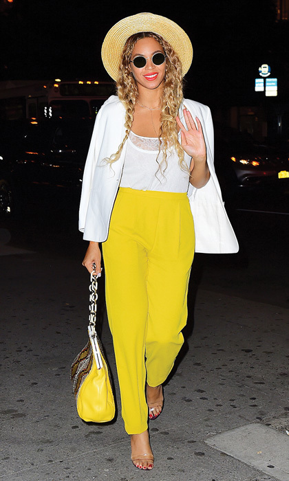 Beyoncé, the queen of our lemonade cravings, paired yellow trousers with a yellow-trimmed handbag, crisp white tops and a summer-ready wide-brimmed hat.
