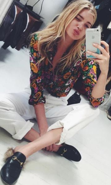 The model pares back a bold patterned shirt with white trousers and mannish loafers.