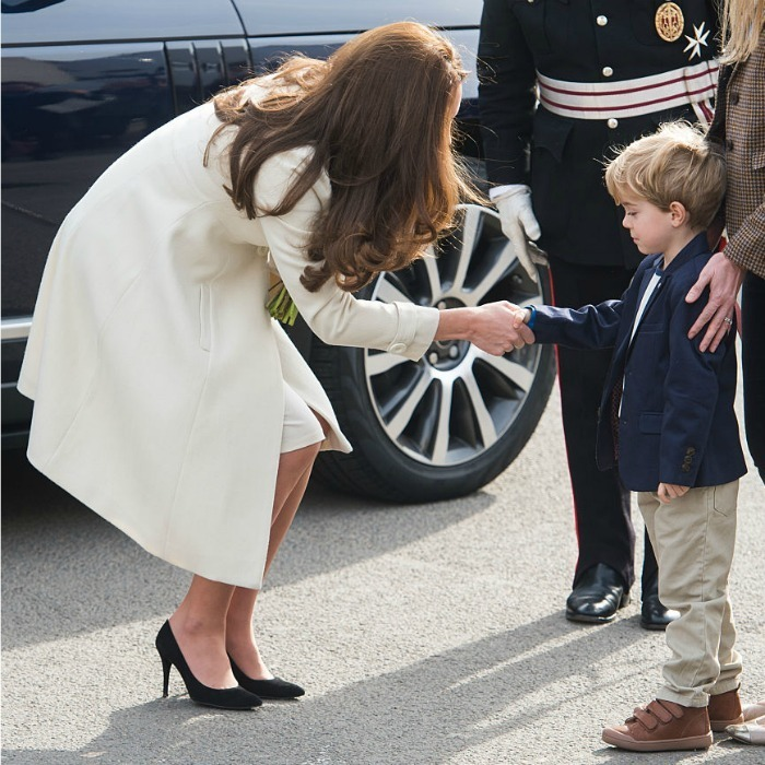 Suspicious of the duchess, a little boy cautiously watched Kate shake his hand as she toured the set of <em>Downton Abbey</em> at Ealing Studios in 2015.