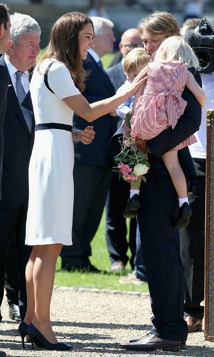 Please do not disturb! One little girl rested on her father's shoulder as Prince George's mom greeted her during a visit to the National Maritime Museum.