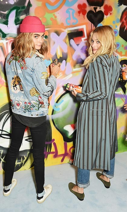 <i>Suicide Squad</i> members Cara Delevingne and Margot Robbie put the finishing touches on a mural by local London graffiti artist Ryan Meades ahead of the film's release on Aug. 5. 