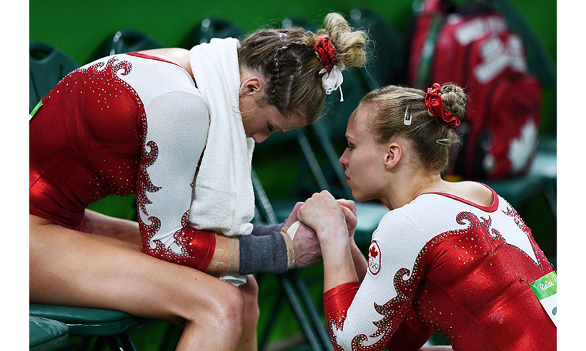 Canada's Ellie Black (R) consoles Brittany Rogers after she suffered a fall on the uneven bars. Team Canada missed qualifying for the team final by less than one point. 