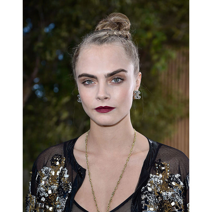 The <em>Suicide Squad</em> actress showed off her gothic side with pale foundation, statement dark berry hued lipstick, and a braided top knot hairstyle. 