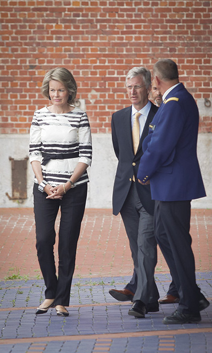 Queen Mathilde looked stylish and demure in a black and white striped blouse and tapered trousers.
