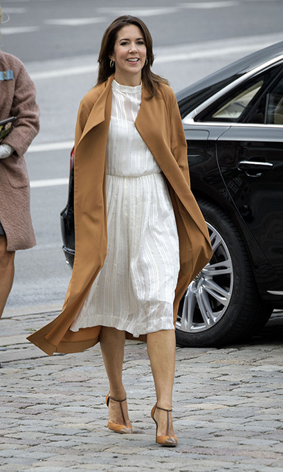 Princess Mary of Denmark looked effortlessly stunning in a long white dress and brown coat, accessorizing with a pair of brown Mary Jane heels.