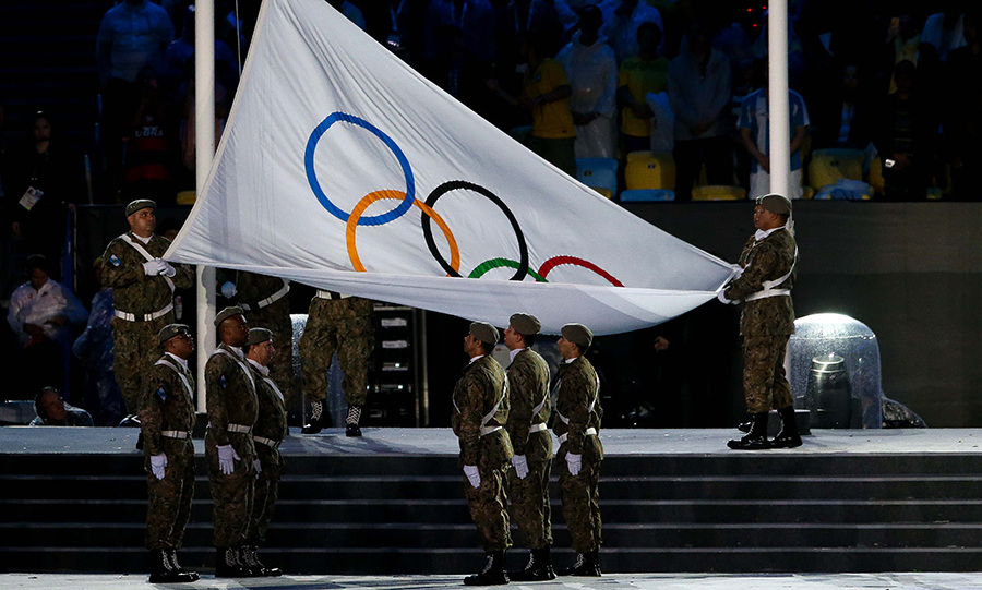 The Olympic flag is lowered inside the stadium. 