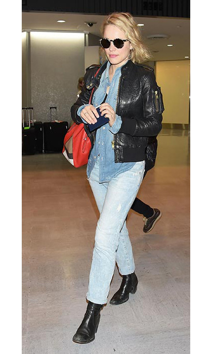 Rachel McAdams does the airport run in boyfriend jeans, denim shirt and black leather. 