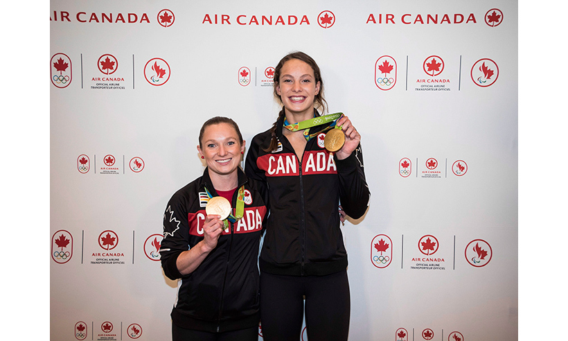 Gold medallists Rosie MacLennan and Penny Oleksiak pose with their medals at Pearson Airport in Toronto.